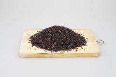 Pilha de arroz preto posta sobre um bloco de desbastamento de madeira Imagem de Stock Royalty Free