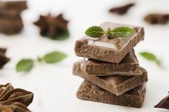 A pilha de barra de chocolate remenda com a hortelã no branco Fotos de Stock Royalty Free