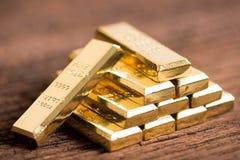 Pilha de barra de ouro no fundo de madeira foto de stock