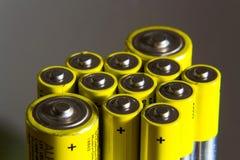 A pilha de baterias amarelas do AA fecha-se acima, conceito do armazenamento da eletricidade Imagens de Stock