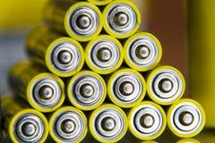A pilha de baterias amarelas do AA fecha-se acima do fundo colorido sumário Foto de Stock