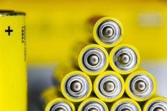A pilha de baterias amarelas do AA fecha-se acima do fundo colorido sumário Fotografia de Stock