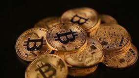 A pilha de bitcoin das moedas de ouro gerencie contra o fundo preto filme