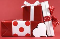 A pilha de caixa de presente festiva do tema vermelho e branco do às bolinhas apresenta com coração branco Fotografia de Stock
