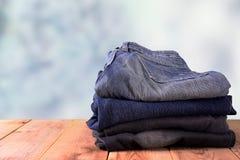 Pilha de calças de brim em de madeira Foto de Stock