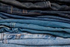 A pilha de calças de brim forma a fundo cores diferentes das camadas da sarja de Nimes Imagens de Stock Royalty Free