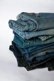 A pilha de calças de brim forma a fundo cores diferentes das camadas da sarja de Nimes Fotos de Stock