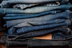 A pilha de calças de brim forma a fundo cores diferentes das camadas da sarja de Nimes Foto de Stock