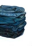 A pilha de calças de brim forma a fundo cores diferentes das camadas da sarja de Nimes Fotografia de Stock Royalty Free