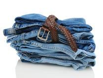 Pilha de calças de ganga da sarja de Nimes com correia Foto de Stock Royalty Free