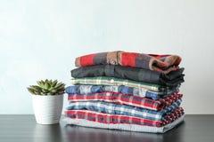 Pilha de camisas coloridas e de planta suculento na tabela imagem de stock