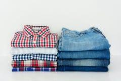 Pilha de camisas e de calças de brim de manta no fundo branco fotos de stock