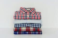 Pilha de camisas de manta no fundo branco imagens de stock