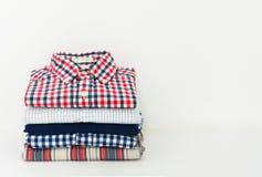 Pilha de camisas de manta no fundo branco fotografia de stock