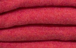 Pilha de camisetas feitas malha de lã vermelhas close-up, textura, fundo imagens de stock royalty free