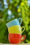 Pilha de canecas coloridas com bokeh Fotografia de Stock Royalty Free