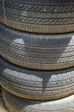 A pilha de carro usado velho empoeirado monta pneus mostrar linhas do sulco imagem de stock