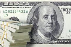 Pilha de cem notas de dólar com uma grande conta no backg Fotografia de Stock Royalty Free