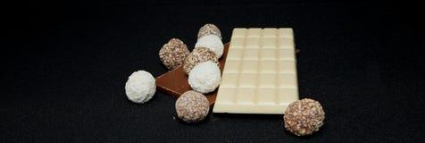 Pilha de chocolate preto e branco isolada no fundo preto, lugar para o texto Foto de Stock Royalty Free