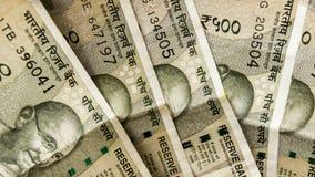 A pilha de cinco cem notas indianas nova da rupia espalhou belamente sobre Parte do líder de Mahatma Gandhi do movimento de indep imagens de stock