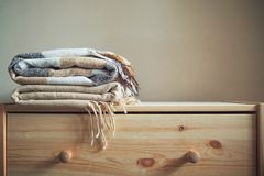 Pilha de coberturas quadriculado bege de lãs em uma caixa de madeira fotos de stock