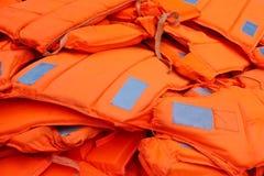 Pilha de colete salva-vidas alaranjados fotografia de stock