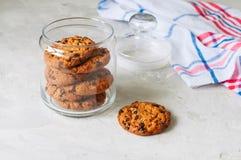 Pilha de cookies caseiros dos pedaços de chocolate no frasco de vidro St branco imagens de stock royalty free