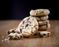 Pilha de cookies dos pedaços de chocolate na tabela de madeira DOF raso Foto de Stock Royalty Free