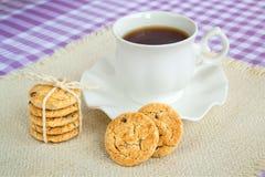 Pilha de cookies de farinha de aveia com partes de copo escuro do chocolate e da porcelana com chá em pires com borda ondulada Pe foto de stock royalty free