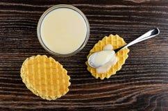 Pilha de cookies, leite condensado na colher na cookie, bacia com leite condensado na tabela de madeira Vista superior foto de stock