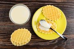 Pilha de cookies, leite condensado na colher na cookie nos pires, bacia com leite condensado na tabela de madeira Vista superior fotografia de stock