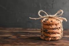 Pilha de cookies saborosos dos pedaços de chocolate na tabela de madeira fotos de stock royalty free