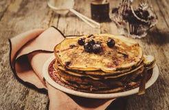 Pilha de crepes recentemente cozidos caseiros das panquecas com as bagas do corinto preto Fotografia de Stock