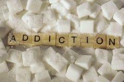 Pilha de cubos do açúcar e de palavra do apego em letras de bloco como recomendam nas calorias adicionais e no abuso insalubre do fotos de stock