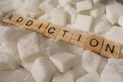 Pilha de cubos do açúcar e de palavra do apego em letras de bloco como recomendam nas calorias adicionais e no abuso insalubre do imagem de stock royalty free