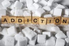 Pilha de cubos do açúcar e de palavra do apego em letras de bloco como recomendam nas calorias adicionais e no abuso insalubre do foto de stock