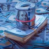 Pilha de dólares, o rolo dos dólares no fundo de cem notas de dólar Projeto azul imagem de stock