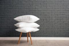 Pilha de descansos de cama macios na cadeira perto da parede de tijolo imagens de stock