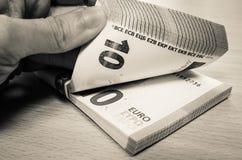 Pilha de dez contas do Euro em uma mesa do pinho, sendo contado foto de stock royalty free