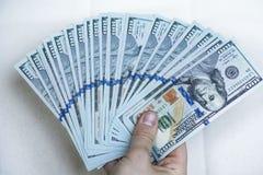 Pilha de dinheiro à disposição em um fundo branco Foto de Stock Royalty Free