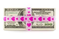Pilha de dinheiro amarrada acima pela fita cor-de-rosa com corações Fotografia de Stock Royalty Free