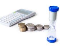 A pilha de dinheiro com calculadora e ampulheta isolou a parte traseira do branco Imagem de Stock