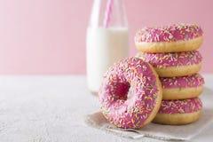 Pilha de donats cor-de-rosa e brancos com a garrafa do leite sobre os vagabundos brancos Imagens de Stock