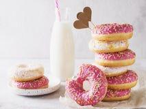 Pilha de donats cor-de-rosa e brancos com a garrafa do leite sobre os vagabundos brancos Fotografia de Stock Royalty Free