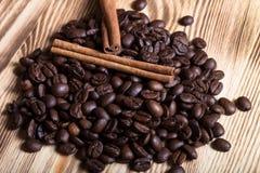 Pilha de feijões de café com canela na tabela de madeira para o backgroun Fotografia de Stock Royalty Free