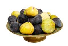 Pilha de figos pretos e amarelos na placa. imagens de stock
