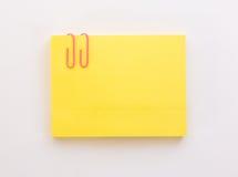 Pilha de folhas de papel amarelas com clipe de papel cor-de-rosa em um branco Foto de Stock Royalty Free