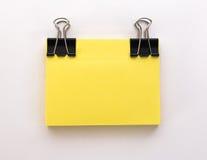 Pilha de folhas de papel amarelas com clipe de papel preto em um branco Fotos de Stock