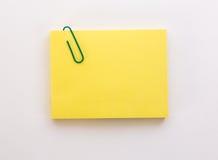 Pilha de folhas de papel amarelas com clipe de papel verde em um branco Fotografia de Stock