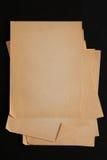 Pilha de folhas velha do papel do ofício isolada no fundo preto Imagem de Stock Royalty Free